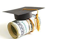 Roll of $100 bills with a graduation cap on top