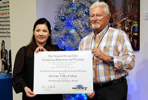 Photo of 2 individuals accepting award