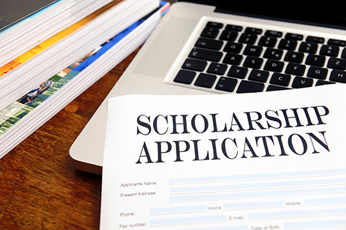 Photo of a Scholarship Application lying on top of a laptop computer